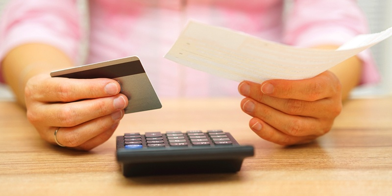 Man holding check and credit card over calculator on desk