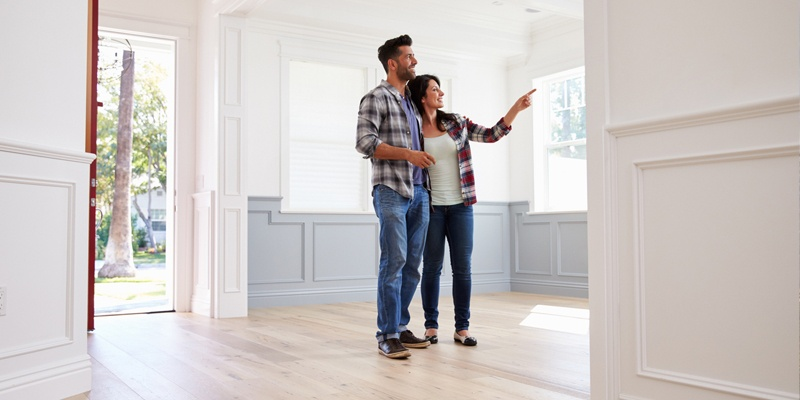 Couple pointing at details in beautiful lit empty home