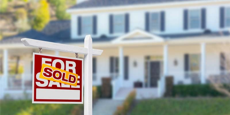 House blurred in background with For Sale sign