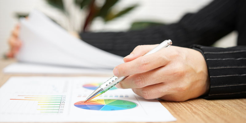 Man pointing at graph on table with pen