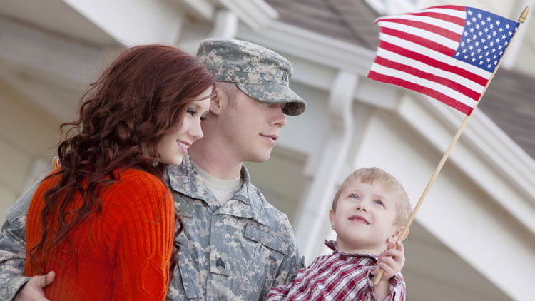 Military family with little boy holding American flag