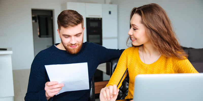 Couple looks over refinancing paperwork for mortgage