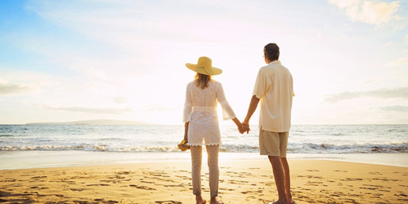Older couple looking out at horizon and ocean on beautiful beach