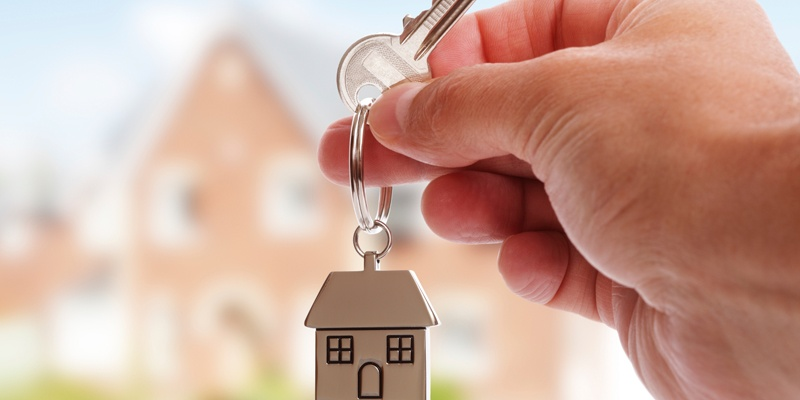 Hand holding House Keys with House Keychain