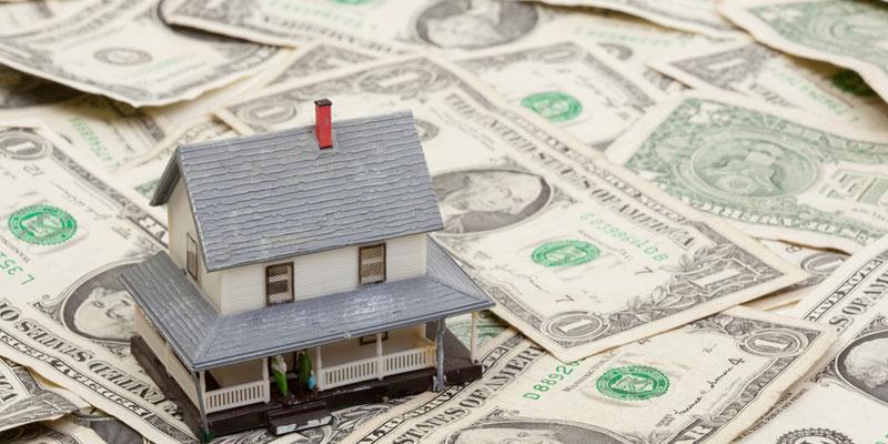 Toy Replica House sitting on dollar bills