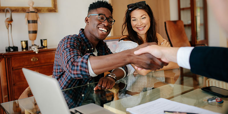 black and asian woman shaking hands on a mortgage agreement