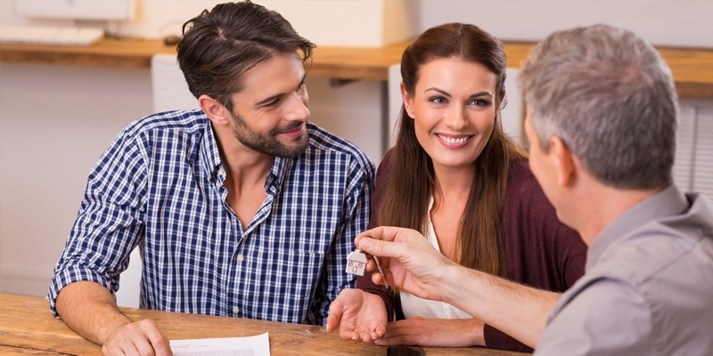 Couple working with mortgage worker and handing keys