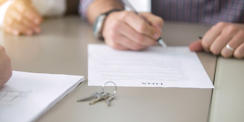 Hand filling out Loan document