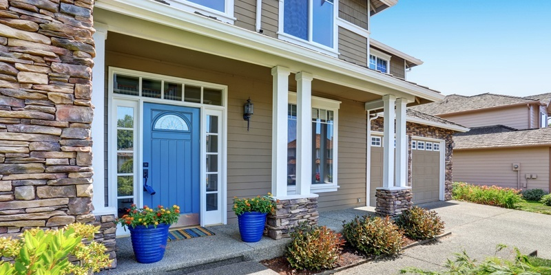 Home with Blue door, tan siding and dormers