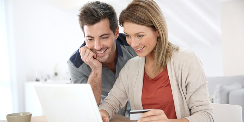 Couple looking at computer and paying