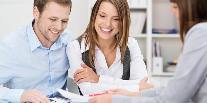 Couple joyfully signing mortgage documents
