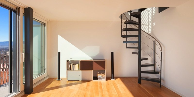 Spiral staircase with hardwood floors and excellent natural light