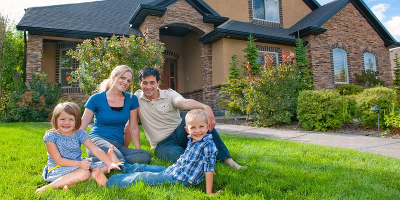 Couple on lawn in front of new home