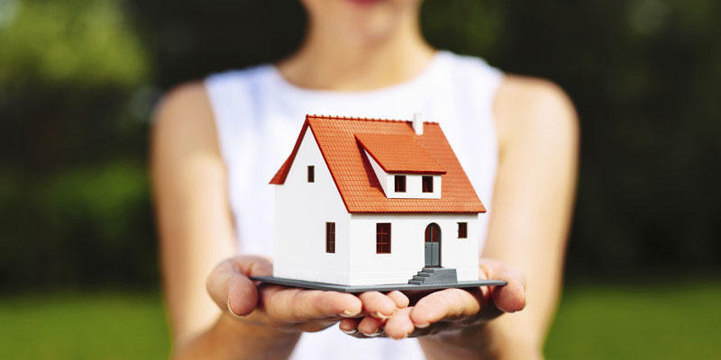 Woman holding small replica of house in both hands