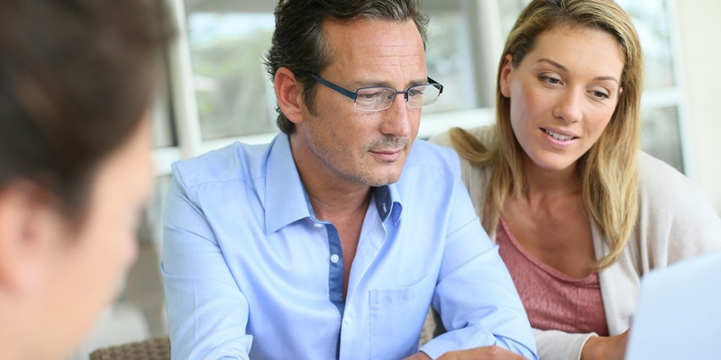 Middle aged man and wife looking at documents