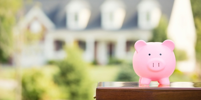 Piggy Bank in front of blurred home